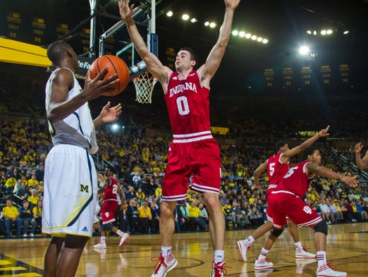 Michigan guard Caris LeVert, left, defended by Indiana forward Will Sheehey (0), tries to inbound the ball in the first half of an NCAA college basketball game in Ann Arbor, Mich., Saturday, March 8, 2014. (AP Photo/Tony Ding)
