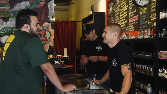 Customer Parker Hurley, left, talks with Matthew Nathan, right, owner of Vapeology, located on Raymond Avenue in the Town of Poughkeepsie.