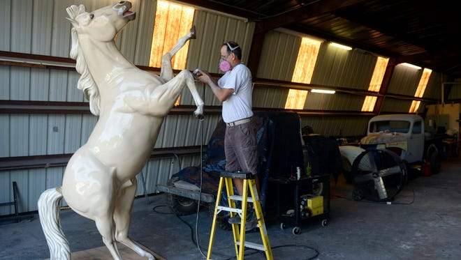"""Todd Biron smooths out repair work being done on Patriot, a statue usually seen in Pocahontas Park in Vero Beach, in his shop, Todd Biron's Classic Restoration on Dec. 7, 2016. The statue suffered major damage as Hurricane Matthew passed near the Treasure Coast in October. """"When the statue finally got to my shop the tail was broken, one of the front legs was severely damaged and there were several puncture wounds,"""" Biron said. """"This statue has been around for as long as I can remember. It's pretty much the remnant of my childhood that still exists in the park."""" Biron said he will be working on the statue at least two days a week and hopes to have it ready before the Hibiscus Festival in April."""