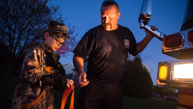 Isaac Konzel receives some candy from Penn Township firefighters during trick or treat night in Penn Township on Tuesday, Oct. 24, 2017.