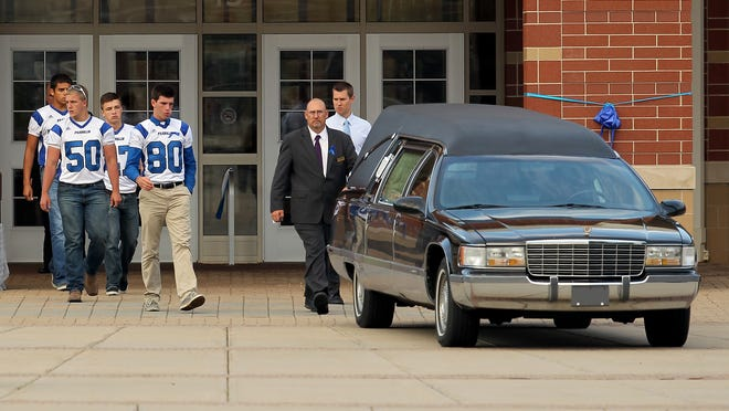 Members of the Franklin High football team exit the high school gymnasium, during a memorial service on Wednesday, June 11, 2014, for Jason Moran. Moran and Michael Chadbourne died after coming to the aid of their friend, Sarah McLevish, who was swept below part of a low-head dam, while they were all swimming in the Big Blue River in southern Johnson County.
