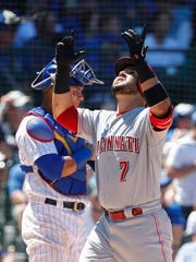 Reds' Eugenio Suarez scores against the Cubs at Wrigley Field on Sunday.
