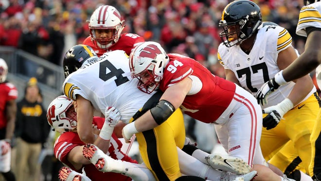 Conor Sheehy (94) and Andrew Van Ginkel (left)  combine to sack Iowa quarterback Nathan Stanley on Saturday at Camp Randall Stadium.