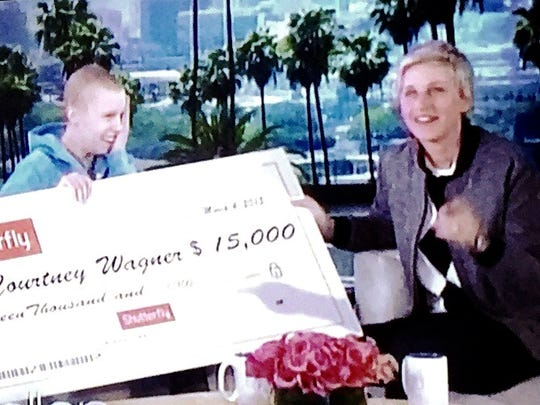 Ellen DeGeneres gives Courtney Wager a check for $15,000.