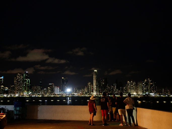 People enjoy a walk at dusk with the Panama City skyline