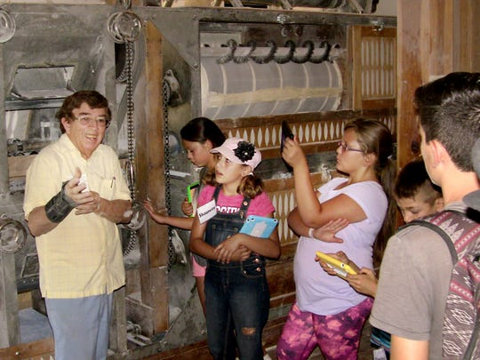 Jose Cordova, owner of Valencia Flour Mill, explains how the mill grinds wheat into flour to participants in the Food Camp for Kids program held by New Mexico State University's Cooperative Extension Service in Valencia County.