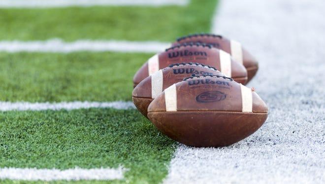 Gameballs sit on the sideline before the start of an IHSAA high school football game at Center Grove High School, Friday, September 8, 2017.
