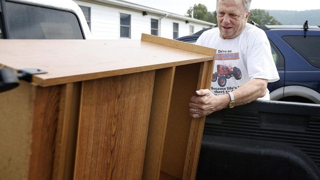 Mike Givens, the high school math and sceince teacher at North Spencer Christian Academy, removes a donated shelving unit from the bed of his truck after picking it up from a Candor dentistry.