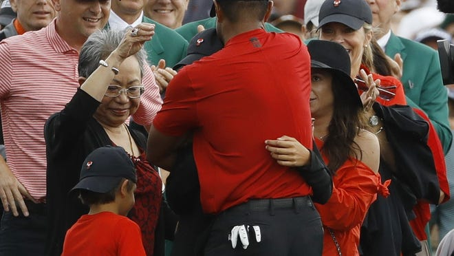 Tiger Woods, seen here celebrating with his family after his 2019 Masters win, was filled with emotion when joining CBS for the replay the golf tournament's final round Sunday.