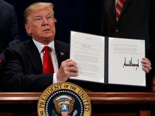 """President Donald Trump holds up a """"Presidential Memorandum Promoting the Reliable Supply and Delivery of Water in the West,"""" after signing it during a ceremony, Friday, Oct. 19, 2018, in Scottsdale, Ariz. (AP Photo/Carolyn Kaster)"""