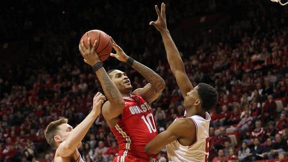 Mar 2, 2014; Bloomington, IN, USA;  Ohio State Buckeyes forward LaQuinton Ross (10) shoots the ball with Indiana Hoosiers forward Troy Williams (5) and forward Jeff Howard (24) defending the play during the second half at Assembly Hall. Indiana won 72-64. Mandatory Credit: Pat Lovell-USA TODAY Sports