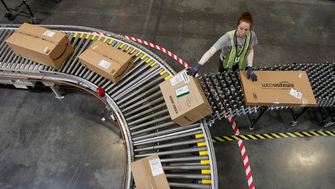 An Amazon employee moves packages at a fulfillment center in Goodyear, Ariz.