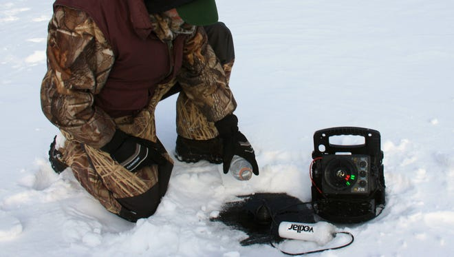 By placing the electronics transducer in a puddle of water, anglers can take sonar readings right through the ice.