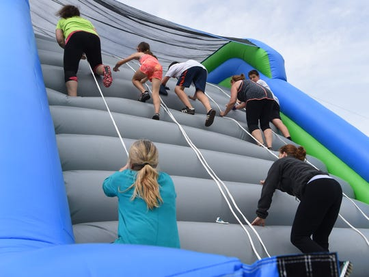 Runners climb one of the inflatables at the finish