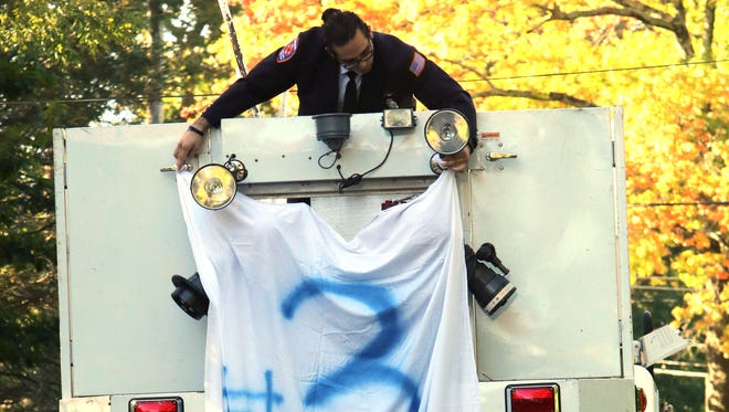 Ray Zimlin, a teammate of Robby Schartner and a Purchase volunteer firefighter, hangs a sheet with Schartner's uniform number from the bucket of Tower Ladder 53 on Wednesday before the start of Schartner's funeral.