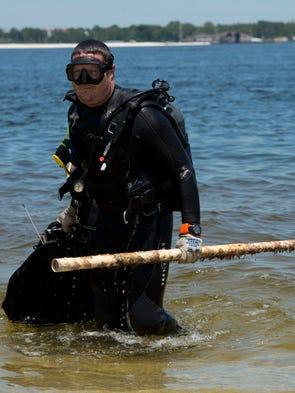 Volunteer diver Kuris Freeland brings in a load of