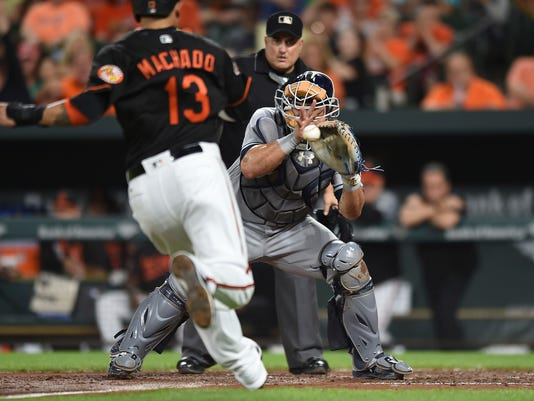 Tampa Bay Rays catcher Wilson Ramos, right, awaits the throw as Baltimore Orioles' Manny Machado races to home in the third inning of a baseball game, Friday, Sept. 22, 2017, in Baltimore. Machado was tagged out on the play. (AP Photo/Gail Burton)