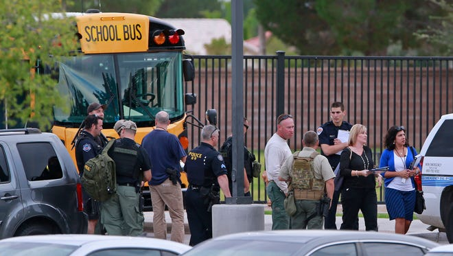 Police and faculty stand outside Fulton Elementary School in Chandler on Tuesday, Oct. 20, 2015.  The school was one of three in the Valley that received bomb threats Tuesday afternoon.