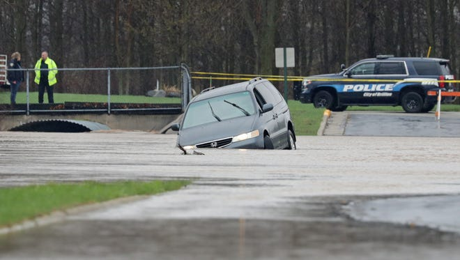 A vehicle is stranded Friday morning in deep water on Tesch Road in Brillion after overnight rain caused flooding.