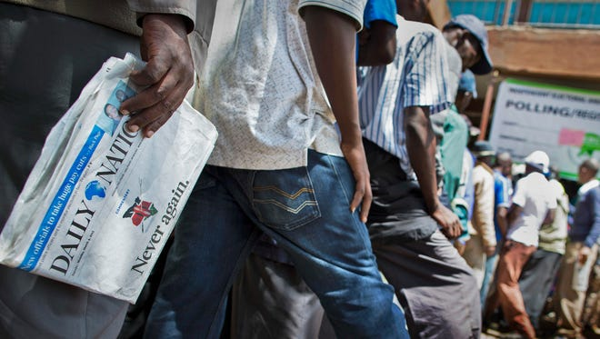 """FILE - In this Monday, March 4, 2013 file photo, a Kenyan voter holds a copy of the Daily Nation newspaper with the headline """"Never again"""" referring to the post-election violence of the previous election in 2007, as he queues to cash his vote at a polling station in the Mathare slum of Nairobi, Kenya."""