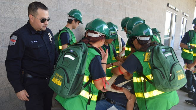 Ralph Mesa of Riverside County emergency services oversees Desert Hot Springs High School students during a recent emergency response drill.