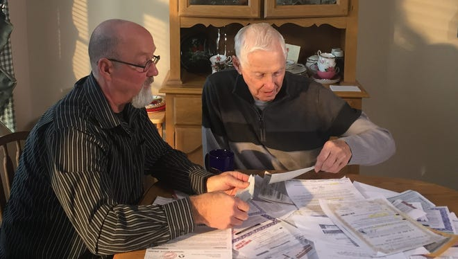 Dan Dean with dad looking through old sweepstakes mailings.