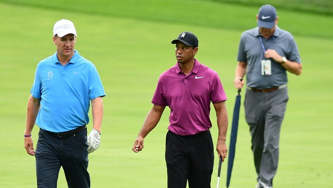 Peyton Manning, left and Tiger Woods walk on the fairway of the eleventh hole during the pro-am for the the Memorial golf tournament May 30.