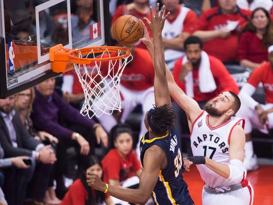 Toronto Raptors centre Jonas Valanciunas (17) dunks the ball past Indiana Pacers forward Myles Turner (33) during Game 7 of round one NBA playoff basketball action in Toronto on Sunday, May 1, 2016. (Nathan Denette/The Canadian Press via AP)