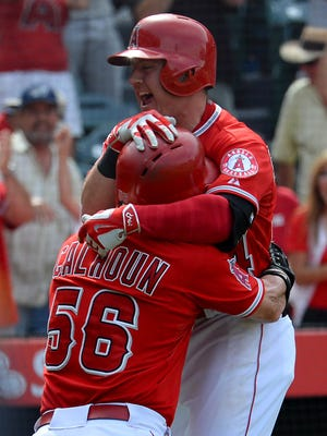 Los Angeles Angels left fielder Daniel Robertson (44) celebrates with right fielder Kole Calhoun (56) after he scored the winning run in the tenth inning off a wild pitch by Seattle Mariners relief pitcher Tom Wilhelmsen (54) at Angel Stadium of Anaheim.Angels won 3-2.
