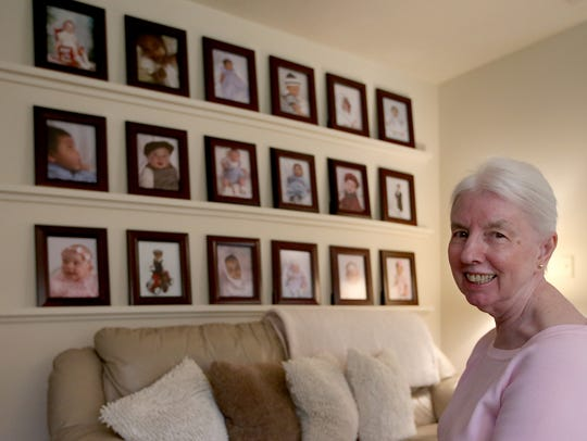 Photographs of Mary Jones' foster children on the wall of her home.