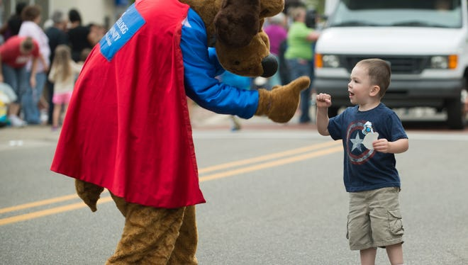 2 year old Eoin Bailey fist-bumps Dollar Dog during the Cereal Festival parade Friday night.