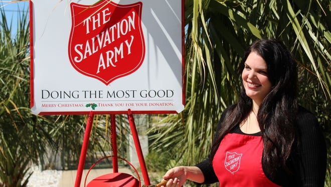 Holly Tremont, a Salvation Army volunteer, rings the bell at one of The Salvation Army's red kettles. The Salvation Army is seeking bell ringers for its kettle locations in Martin and St. Lucie counties.