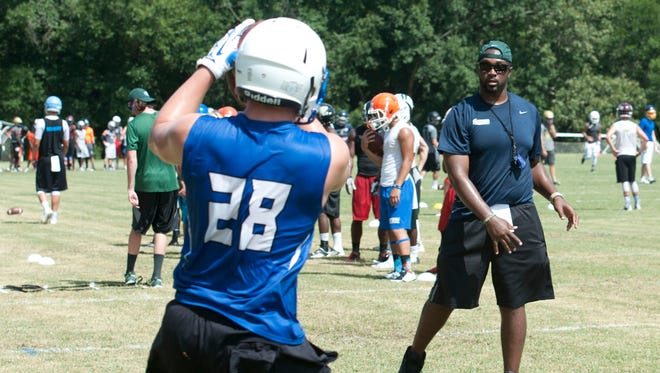 Volunteer coach Kendrick Cook works with a group of receivers during the first University of West Florida football camp Monday morning July 14, 2014.
