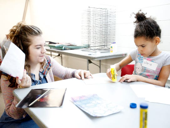 Azaria McCrory, 7, assembles a sketch book with help