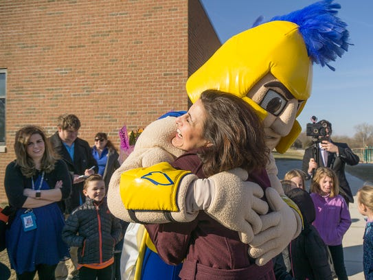 Lisa Rice hugs the Madonna University mascot. She earned her undergraduate and masters degrees from the school.
