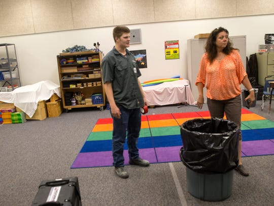 Benjamin Kranz, a water technician with Mooring USA, shows a trash bin filled with water to Candice Thompson, construction and facility coordinator with the Central Consolidated School District, during a tour of the school Thursday at Kirtland Elementary School.