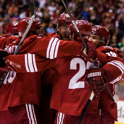 Coyotes players congratulate Oliver Ekman-Larsson (center) after his goal during a game against the Edmonton Oilers at Jobing.com Arena on Friday, April 4, 2014.