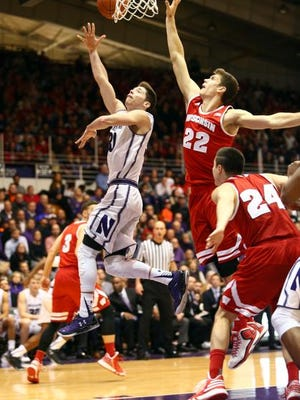Northwestern Wildcats guard Bryant McIntosh (30) goes up for a lay up during the second half while Wisconsin Badgers forward Ethan Happ (22) defends at Welsh-Ryan Arena.