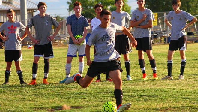 Adam Foltz, front center. attempts a goal kick during practice Wednesday evening at the Riner Steinoff Soccerplex.