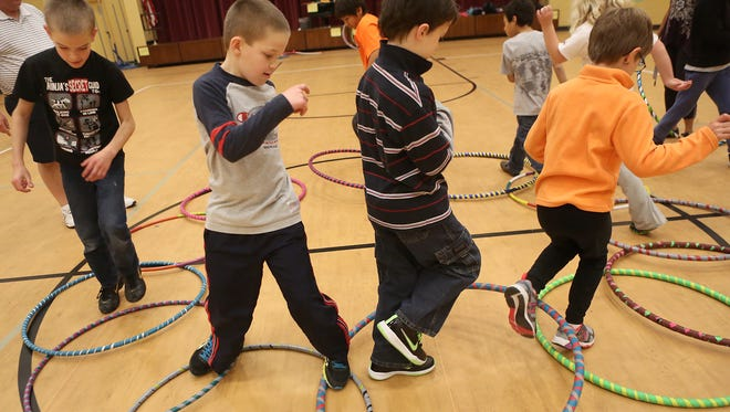 Kids jump through hula hoops during gym class at Springer School and Center in Hyde Park on November 8, 2013.  The Enquirer / Leigh Taylor
