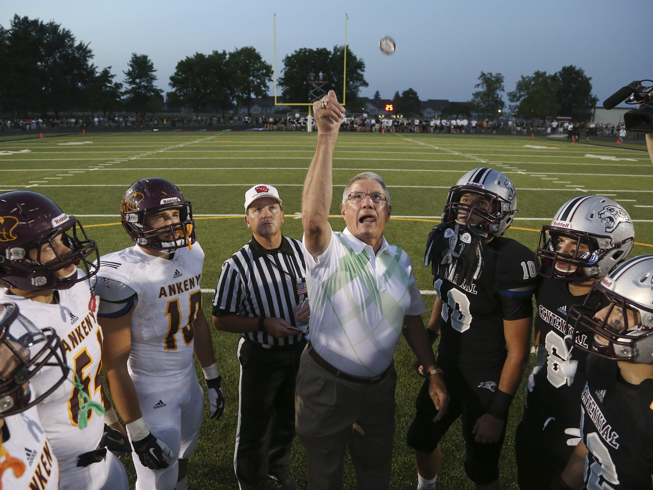 Rick Wulkow flips a coin before the start of a football game between Ankeny High and Ankeny Centennial in 2013. Wulkow has been a visible leader for the Iowa High School Athletic Association over the past decade.