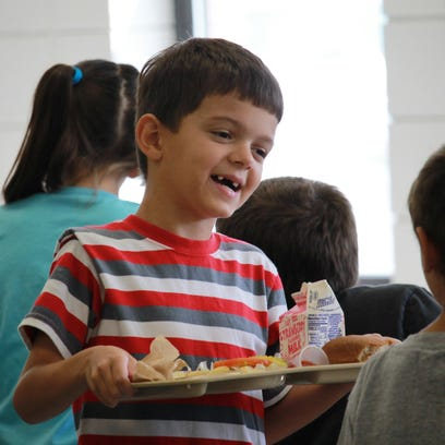 Seven-year-old David Kemp eats a spoonful of fruit during lunchtime Monday at Amanda Gist Elementary. Cotter schools announced Monday that students K-12 will receive free meals.