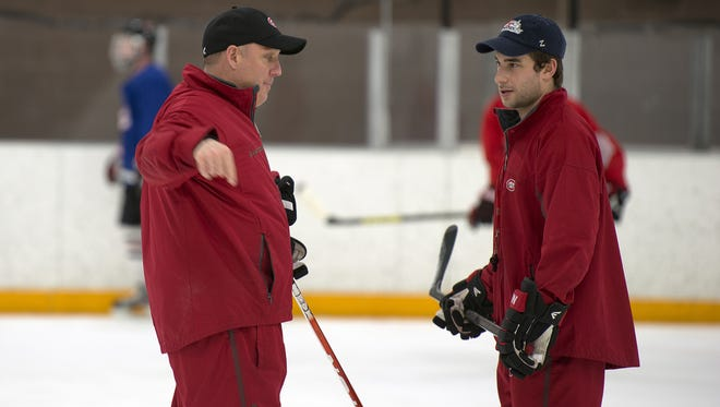 Bob Motzko speaks with assistant coach Garrett Raboin during a 2013 practice at the National Hockey and Event Center in St. Cloud.