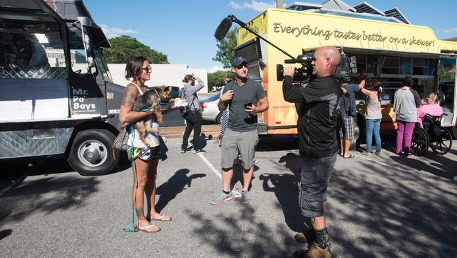 Local resident, Kail Dudley with her dog, Feldspar, offers a critique of a food truck meal to the producers of the Food Network show, Great Food Truck Race, during a taping in downtown Pensacola Wednesday afternoon May 24, 2017.