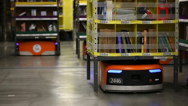 Kiva robots move racks of merchandise at an Amazon fulfillment center on January 20, 2015 in Tracy, California. Kiva robots can fetch merchandise for workers and are capable of lifting up to 750 pounds.