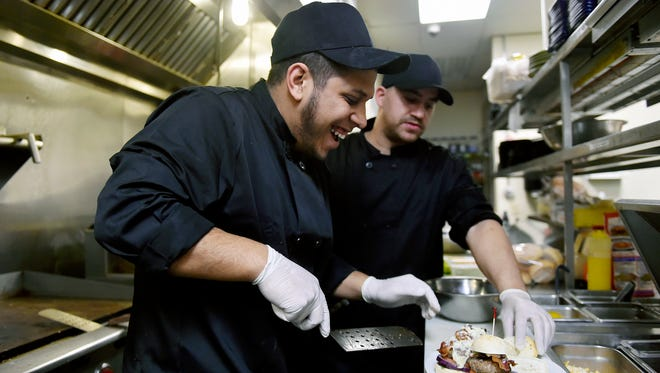 Line cooks Michael Birriel and Lamarr Gray work together to plate sliders at Hogan's Bar & Grill at the Valley Green Golf Course in Newberry Township. The restaurant has passed its three most recent health inspections.