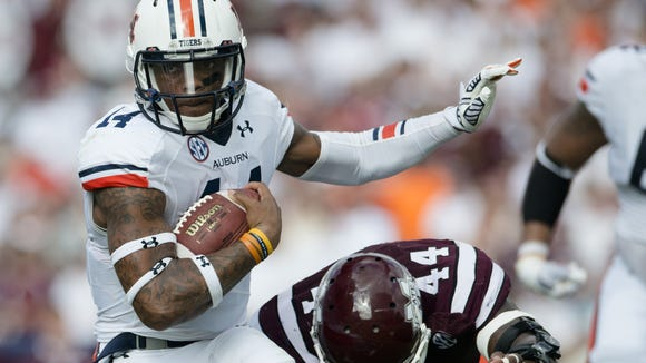 Auburn quarterback Nick Marshall and his teammates remain convinced after Saturday?s loss that they can play their way back into the national championship picture. Auburn quarterback Nick Marshall (14) is tackled by Mississippi State tight end Christian Holmes (44) runs for a first down during the NCAA football game on Saturday, Oct. 11, 2014, between Auburn and Mississippi State at Davis Wade Stadium in Starkville, Miss.