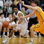 Male guard guard Corey Bowman drives the ball past a defender during the game against St Xavier.