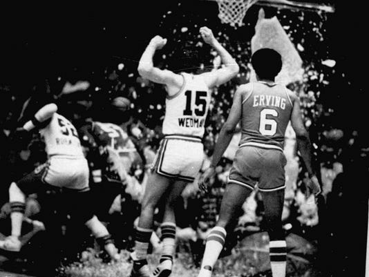 Kansas City Kings' Scott Wedman and Philadelphia 76ers' Julius Erving watching as Kings' Bill Robinzine, left, and 76ers' Darryl Dawkins run for cover after Dawkins shattered the glass backboard during a basketball game in November of 1979 in Kansas City, Missouri.