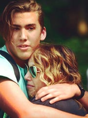 Theo Lassen hugs his mother after safely hiking out